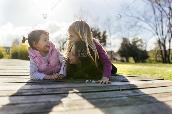 Three smiling girls lying on a boardwalk