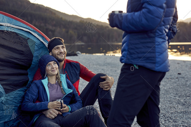 Smiling young couple with friend sitting at tent at lakeshore
