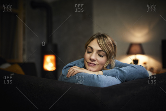 Portrait of woman relaxing on couch at home in the evening