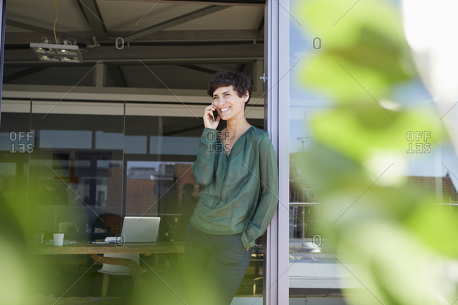 Smiling woman standing at the window talking on cell phone