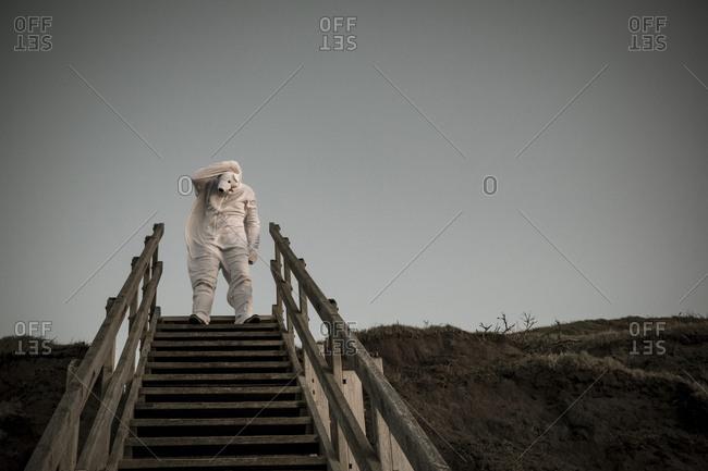 Man wearing ice bear costume on steps- despair