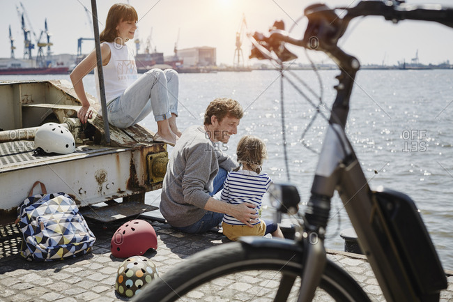 Germany- Hamburg- family having a break from a bicycle tour at River Elbe