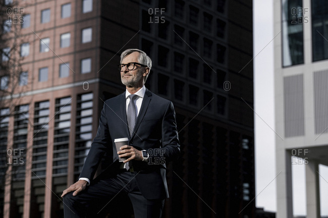 Grey-haired businessman in front of red skyscraper holding coffee to go