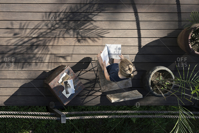Blond girl sitting on terrace- reading book