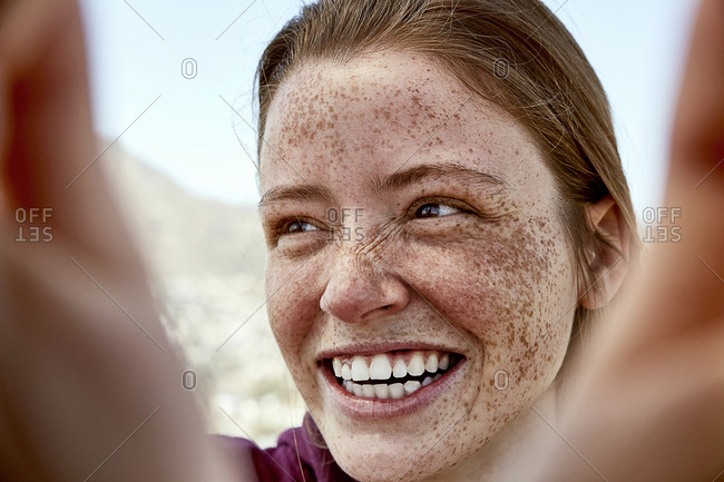 Portrait of laughing young woman with freckles outdoors