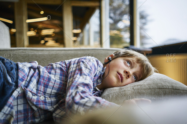 Boy lying on couch with earphones