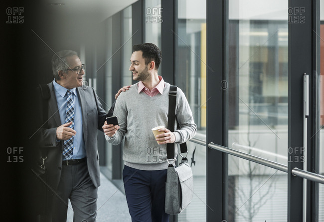 Two businessmen walking and talking on office floor