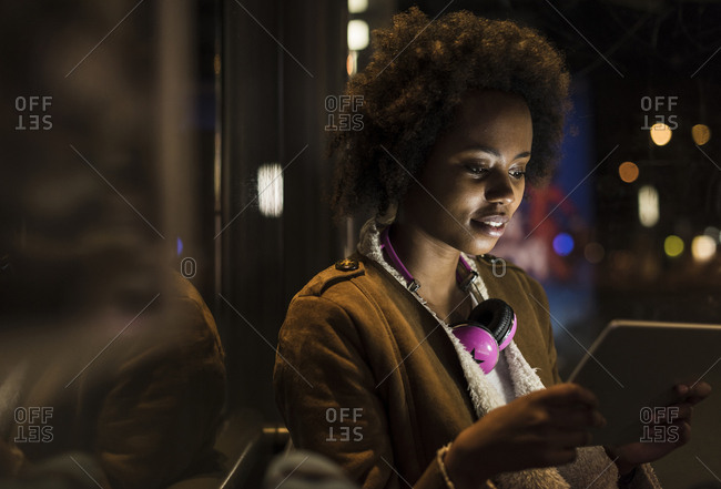 Young woman with headphones using tablet while waiting at the tram stop