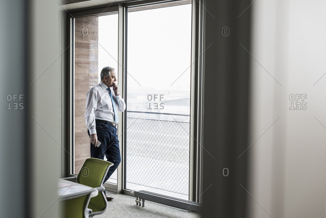 Senior manager in office standing at the window holding smartphone