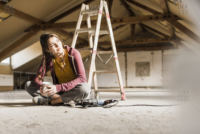 Independent young woman renovating her new home- sitting on floor with cup of coffee