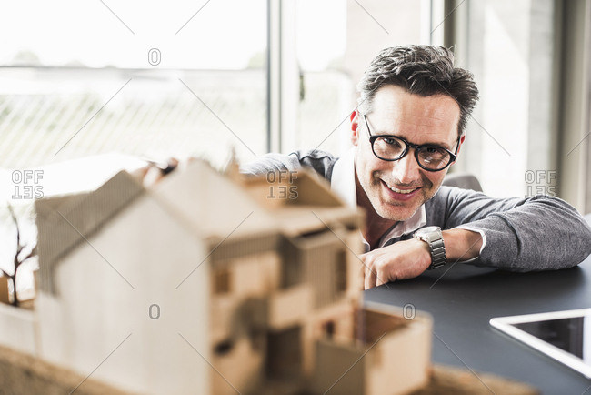 Portrait of smiling architect working on architectural model