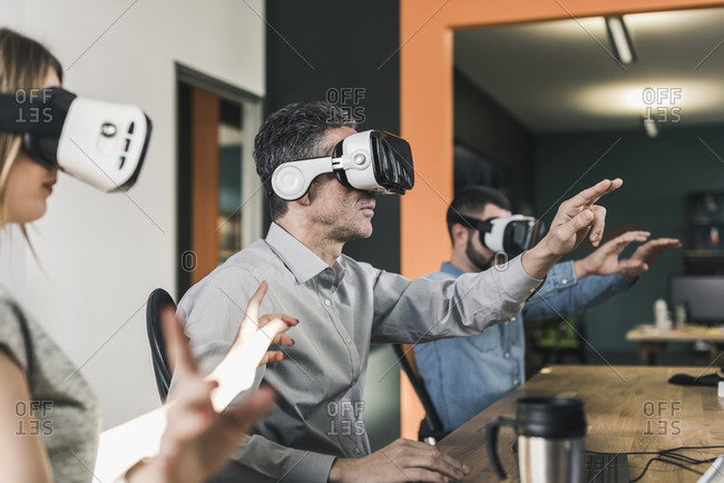 Colleagues wearing VR glasses in office