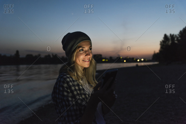 Young woman using smartphone on riverside in the evening
