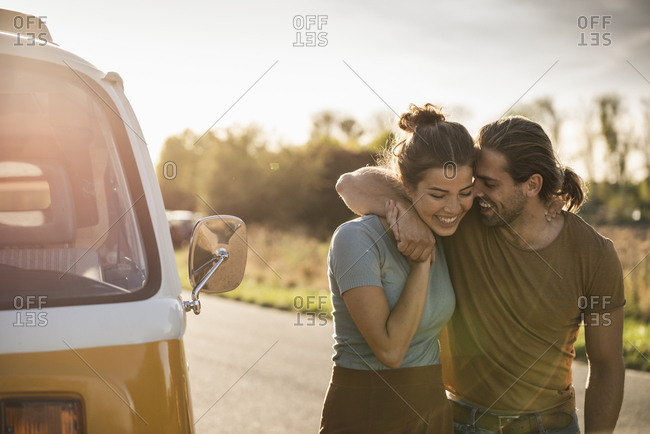 Affectionate couple walking on the road with arms around- next to their camper
