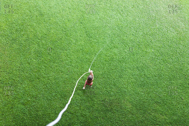 Little boy standing on lawn playing with garden hose- top view