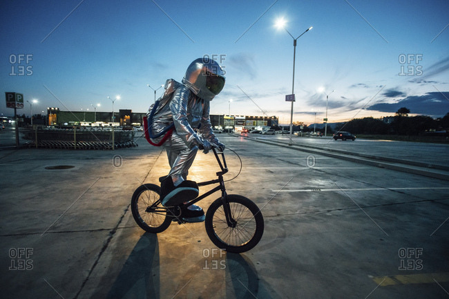Spaceman in the city at night on parking lot riding bmx bike