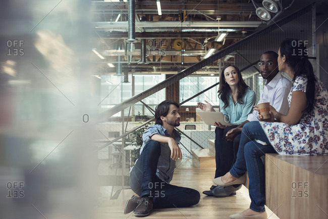 Young business people discussing- sitting on stairs