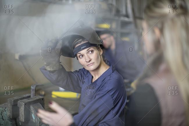 Woman talking to female mechanic in workshop