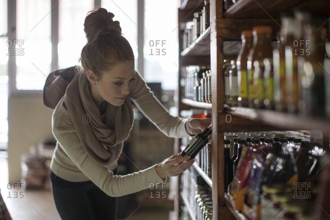 Woman looking at bottle in shelf in shop