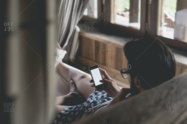 Young man using smartphone lying in bed at home