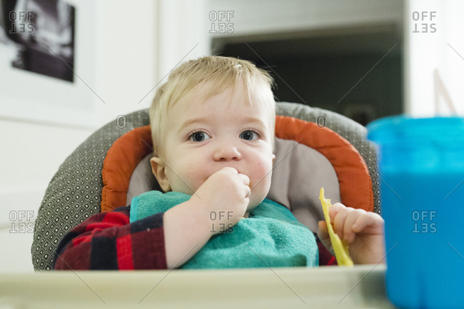 Portrait of cute baby boy eating snacks while sitting on high chair at home