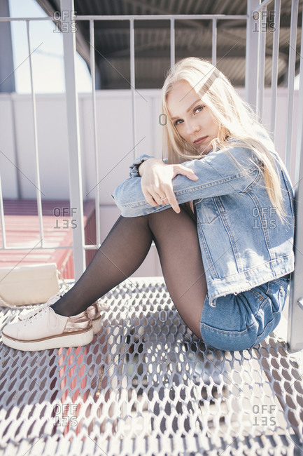 Full length side view portrait of young woman sitting on metal grate by railings in city