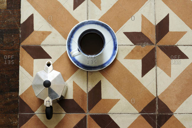 Overhead view of coffee cup with saucer and espresso maker on tiled floor