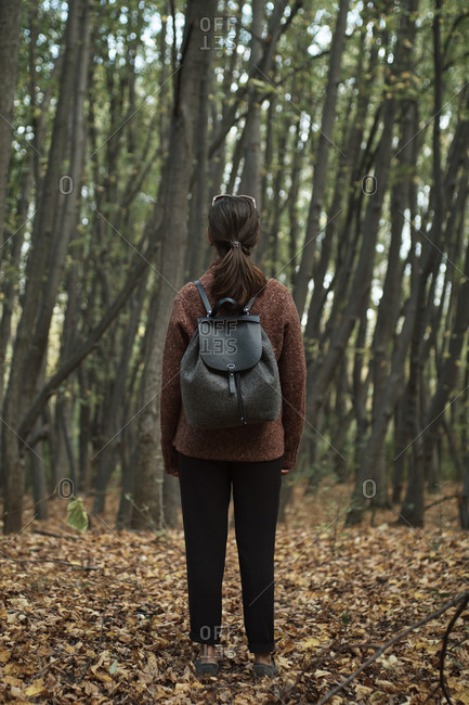 Full length of woman with backpack looking at view while standing in forest during autumn