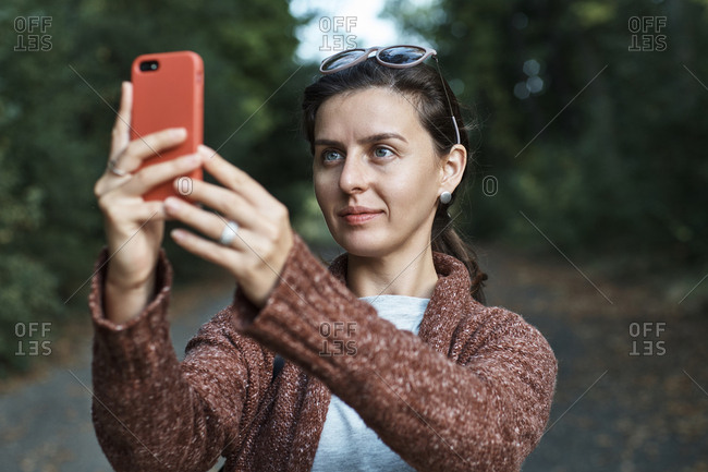 Woman photographing with smart phone while standing in park during autumn