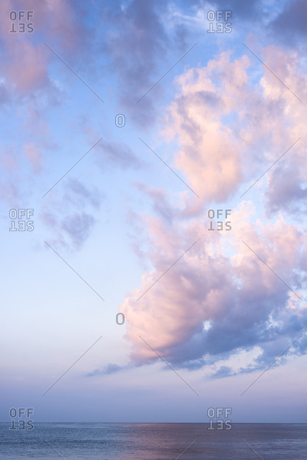 Vertical shot of Cotton Candy pink clouds at sunrise over the ocean