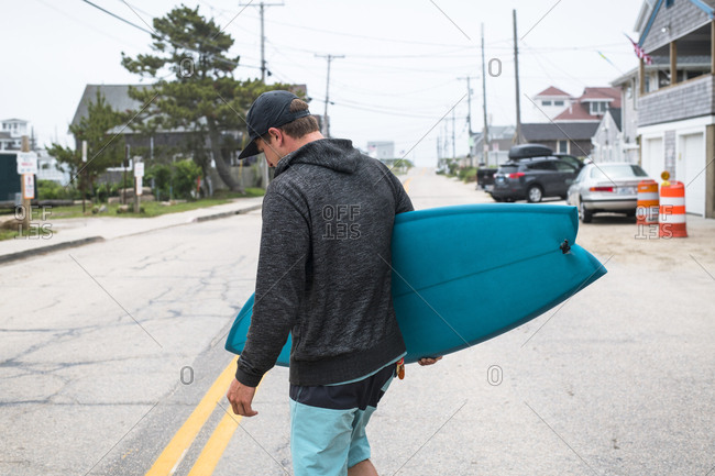 Young man carrying his new blue fish surfboard across the street