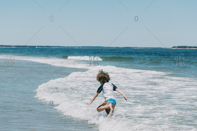 Rear view of playful boy running in sea against clear blue sky during sunny day