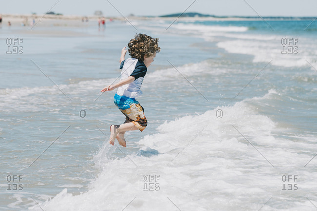 Side view of playful boy jumping in sea during sunny day