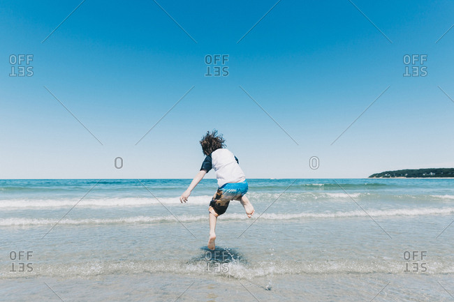 Rear view of playful boy jumping in sea against clear blue sky during sunny day