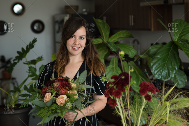 Woman smiling at camera holding bouquet of flowers