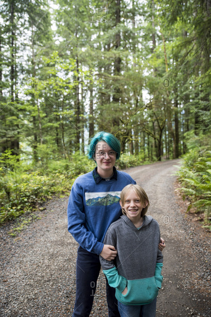 Portrait of happy siblings standing on road amidst trees in Olympic National Park