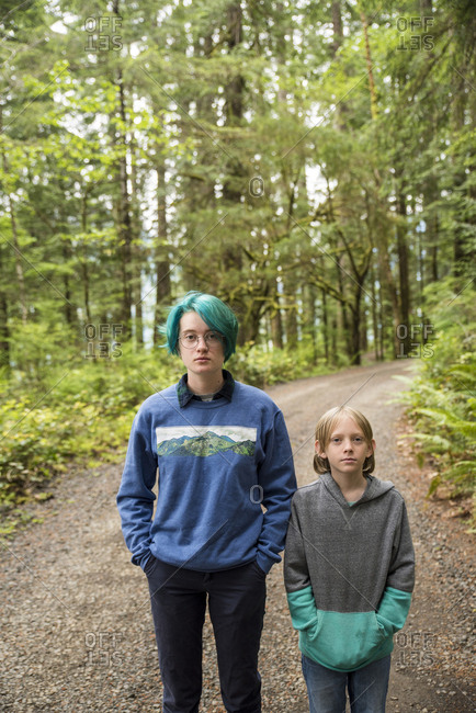 Portrait of siblings standing on road amidst trees in Olympic National Park