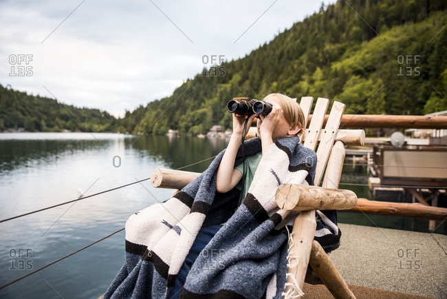 Boy looking binoculars while sitting on chair by lake against mountain at Olympic National Park