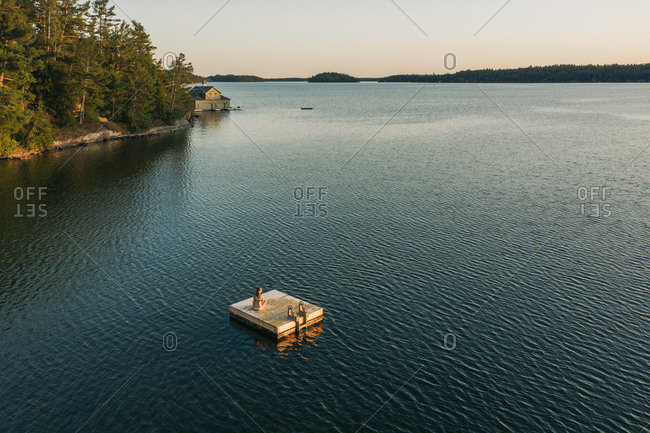 Woman Sitting On Floating Dock In Canadian Lake