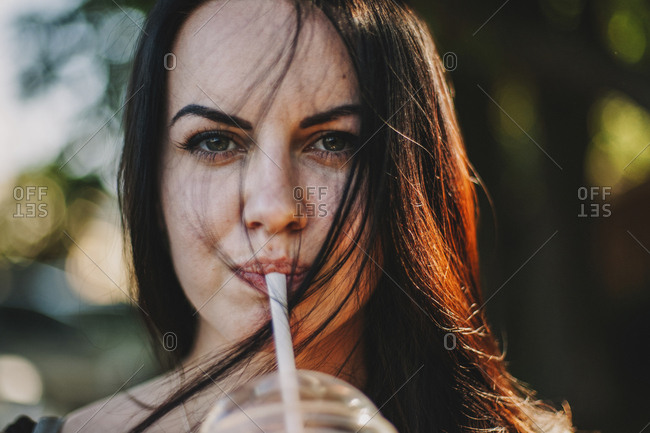 Close-up portrait of woman having drink while standing outdoors