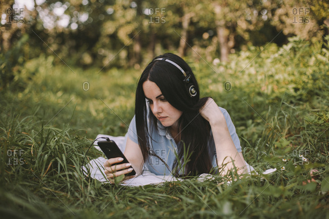 Woman with long hair listening music while using mobile phone on grassy field in garden