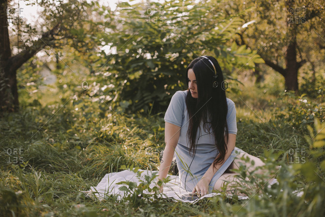 Thoughtful woman with long hair listening music while sitting on grassy field in garden