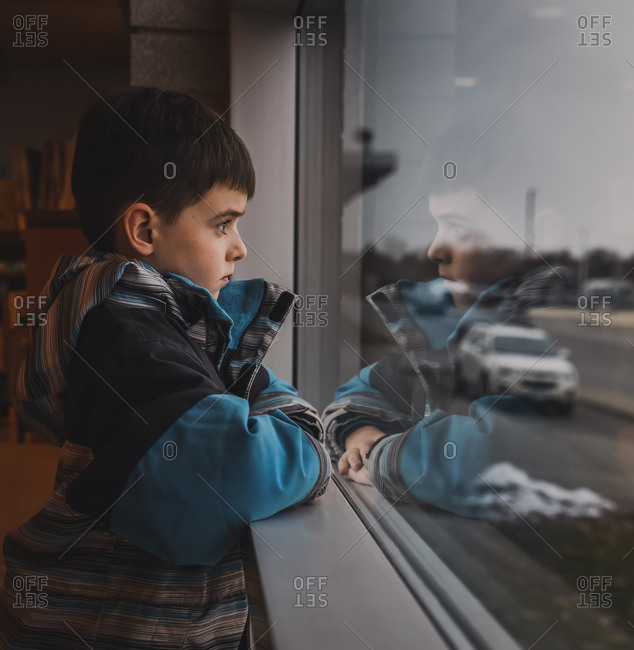Young boy wearing winter coat looking out window at busy street