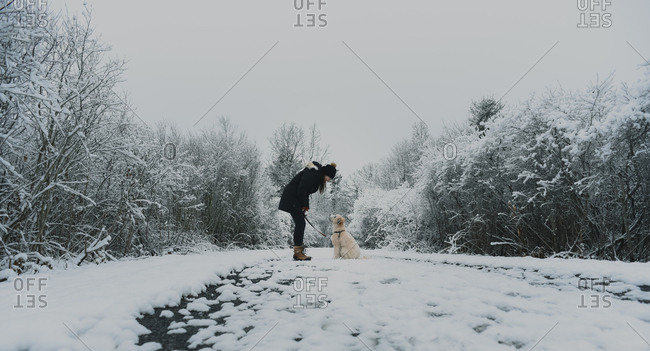 Woman looking down at a fluffy dog on a snowy path in the woods
