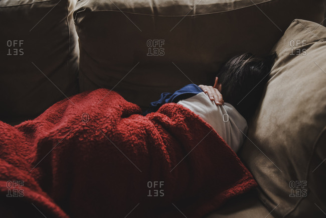 Young boy sleeping on a couch under a blanket facing away