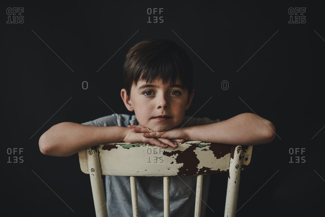 Young boy sitting backwards on old wooden chair looking forward