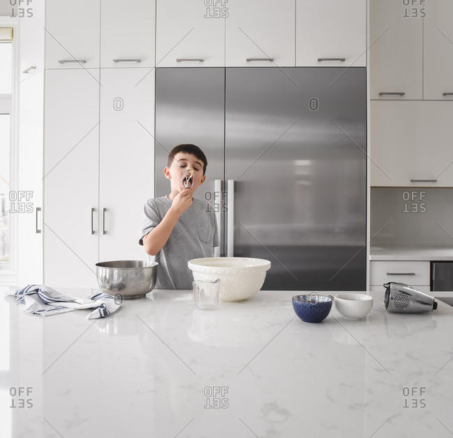 Young boy licking batter off of beater in modern kitchen