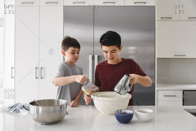 Two boys using a mixer and measuring cup in a modern kitchen