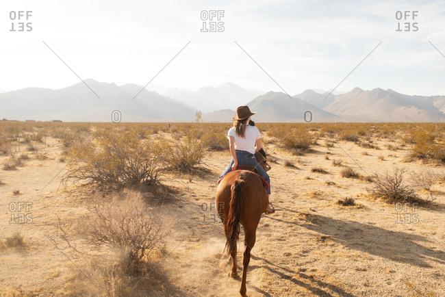 Woman Riding Horse into Mountains