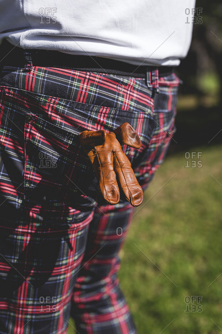 Rear view of man with golf glove in pocket standing at park during sunny day